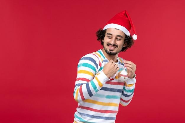 Вид спереди молодой человек держит елочные игрушки на красной стене новый год красные праздники человека