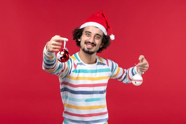 Вид спереди молодой человек держит елочные игрушки на красной стене новогодние красные праздники