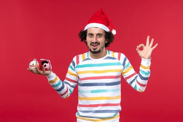 Вид спереди молодой человек держит елочные игрушки на красной стене новый год красный человеческий праздник