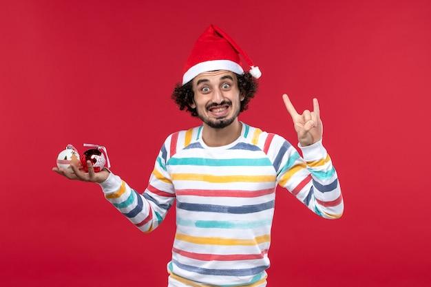Вид спереди молодой человек держит елочные игрушки на красной стене новогодние красные человеческие праздники