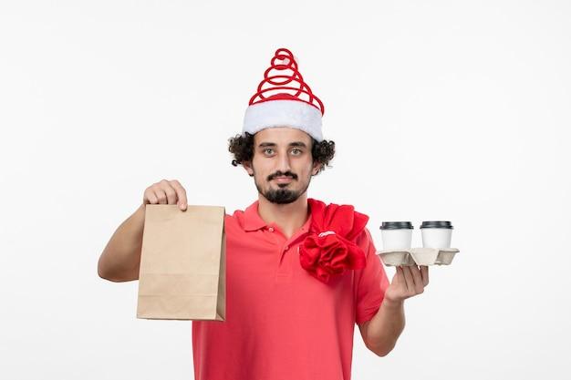 Vista frontale del giovane che tiene il caffè di consegna sul muro bianco
