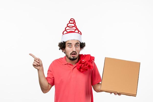 Vista frontale del giovane che tiene la scatola di cibo per la consegna sul muro bianco
