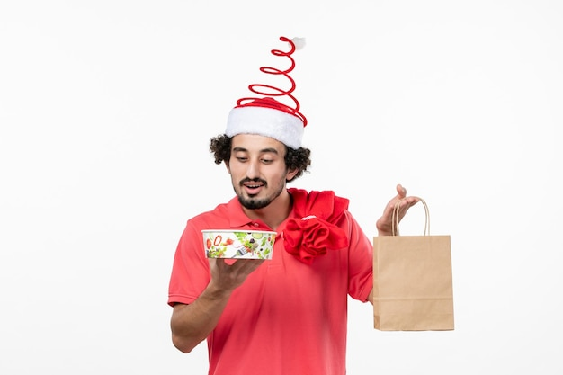 Front view of young man holding delivery food on a white wall