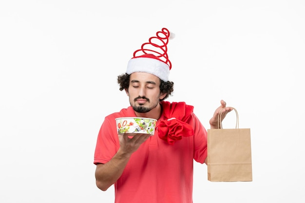 Front view of young man holding delivery food on the white wall