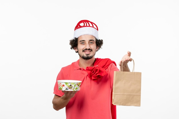 Front view of young man holding delivery food on white wall