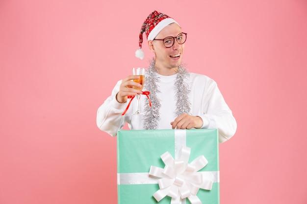 Vista frontale del giovane che tiene bevanda con ghirlande in atmosfera natalizia sulla parete rosa