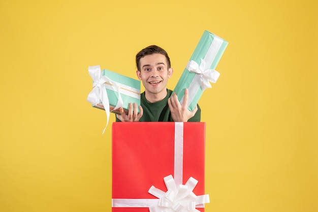 Front view young man holding gifts standing behind big giftbox on yellow