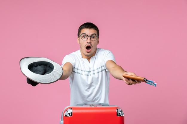 Vista frontale del giovane con cappello e biglietti aerei sulla parete rosa pink