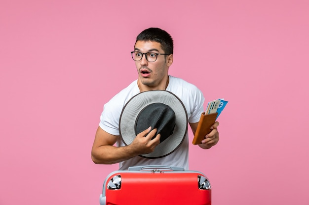 Front view of young man holding hat and plane tickets on pink wall