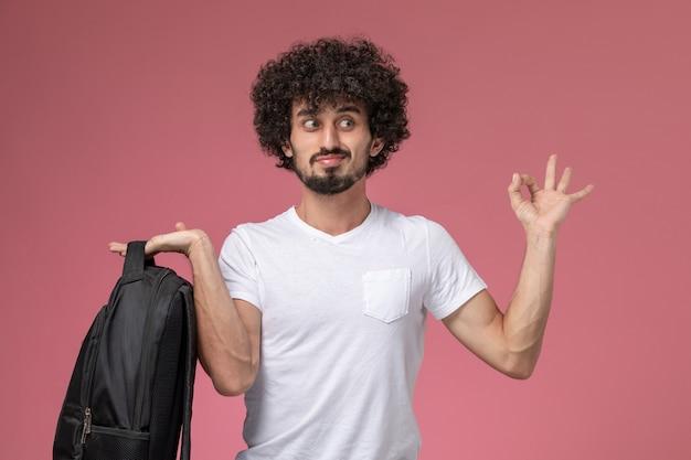 彼のバックパックを保持し、okジェスチャーをしている正面図の若い男
