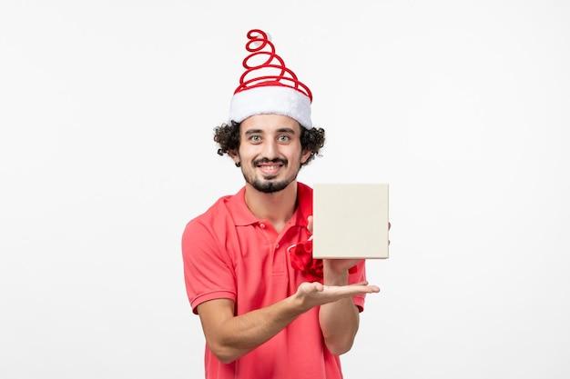 Vista frontale del giovane che tiene il regalo di festa sul muro bianco