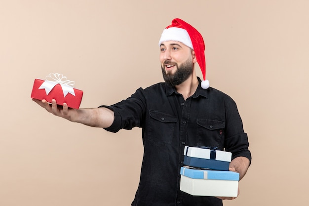 Front view of young man holding holiday presents and giving them on pink wall