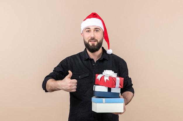 Front view of young man holding holiday presents on a pink wall