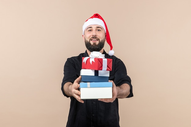 Front view of young man holding holiday presents on pink wall