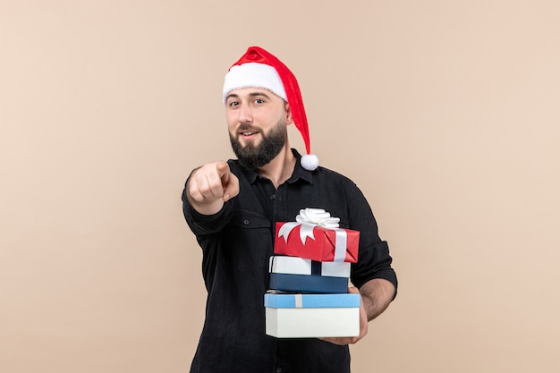 Front view of young man holding holiday presents on the pink wall