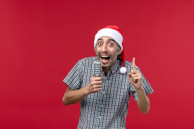 赤い壁の感情の休日の歌手の音楽でマイクを保持している正面図の若い男