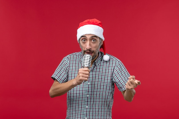 赤い壁の感情の休日の歌手の音楽にマイクを保持している正面図の若い男