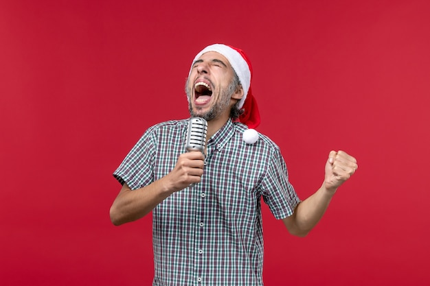 Front view young man holding microphone and screaming on red wall male holiday singer music