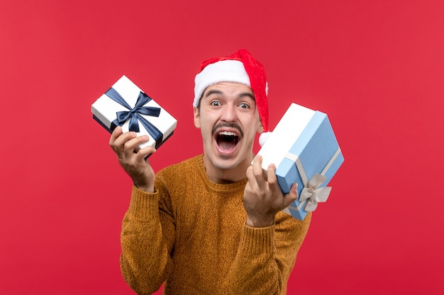 Front view of young man holding new year presents on a red wall