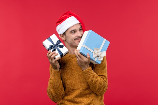 Front view of young man holding new year presents on red wall
