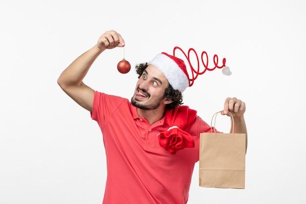 Vista frontale di un giovane che tiene in mano un pacchetto con un regalo sul muro bianco