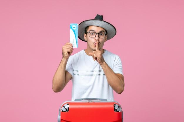 Vista frontale del giovane che tiene il biglietto aereo sulla parete rosa