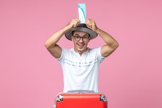 Vista frontale del giovane che tiene il biglietto aereo per le vacanze sul muro rosa