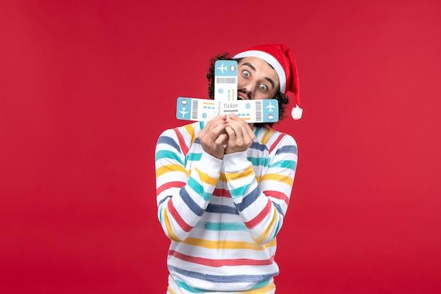 Вид спереди молодой человек, держащий билеты на самолет на красном этаже полета самолета новый год красный