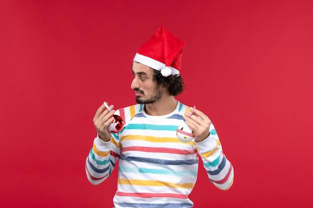 正面図明るい赤い壁にプラスチックのおもちゃを保持している若い男赤い人間の休日新年