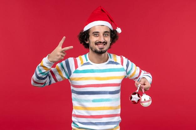 Вид спереди молодой человек, держащий пластиковые игрушки на красном столе, праздники, новогодний красный человек