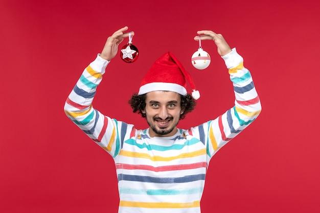Вид спереди молодой человек держит пластиковые игрушки на красном столе красный человеческий праздник новый год