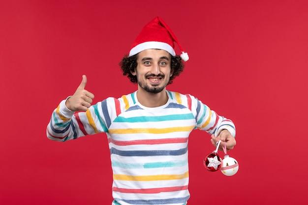 赤い壁の休日新年赤い人間にプラスチックのおもちゃを保持している正面図若い男
