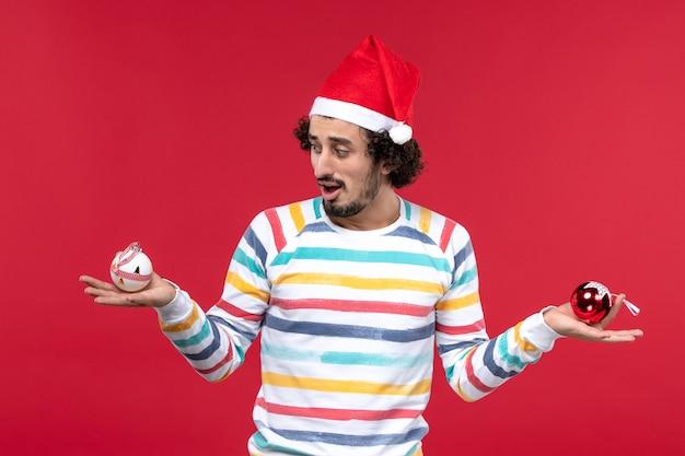 正面図赤い壁にプラスチックのおもちゃを保持している若い男赤い人間の休日新年
