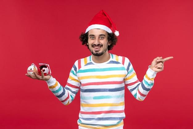 正面図赤い壁にプラスチックのおもちゃを保持している若い男赤い人間の新年の休日