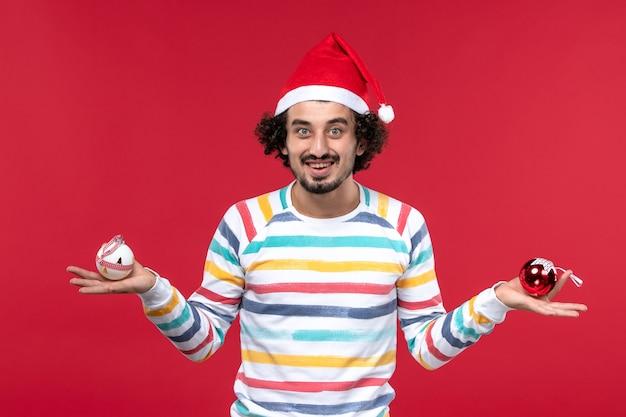 赤い壁に笑顔でプラスチックのおもちゃを保持している正面図若い男人間の休日新年赤