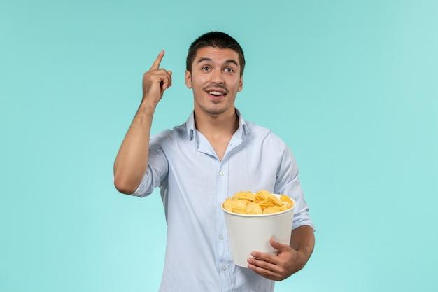 Вид спереди молодой человек держит картофельные чипсы и думает на синей стене одинокий удаленный мужской кинотеатр