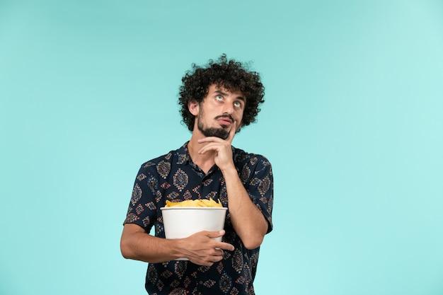 Вид спереди молодой человек, держащий картофельные чипсы и думающий на синей стене, мужской кинотеатр, кинотеатр