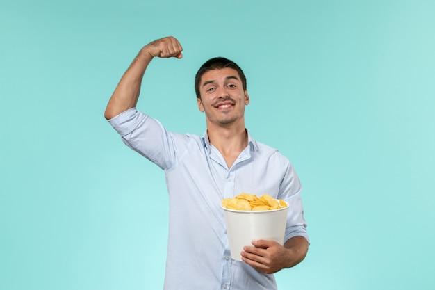 Giovane di vista frontale che tiene le patatine fritte e che flette su un cinema maschio remoto solitario della parete blu