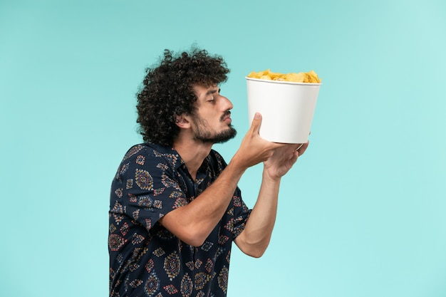 Front view young man holding potato cips on light-blue wall cinema movies film theater male