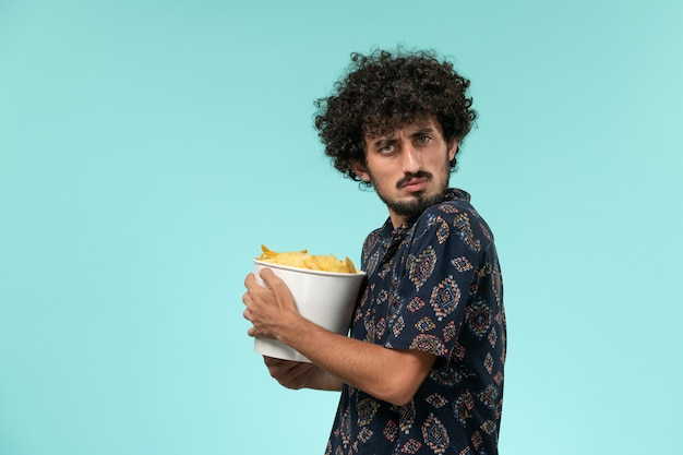 Front view young man holding potato cips on a light blue wall male cinema movie film theater