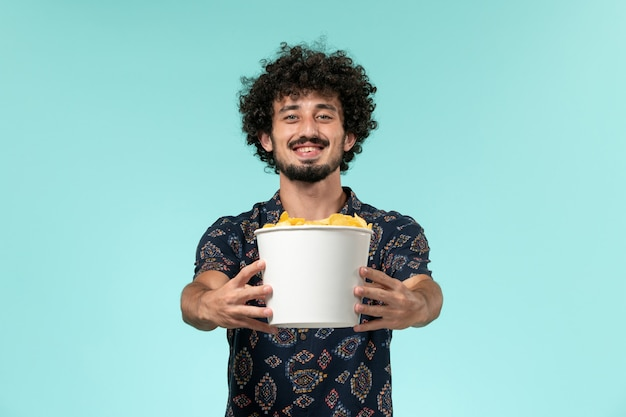 Front view young man holding potato cips on the light-blue wall male cinema movie film theater