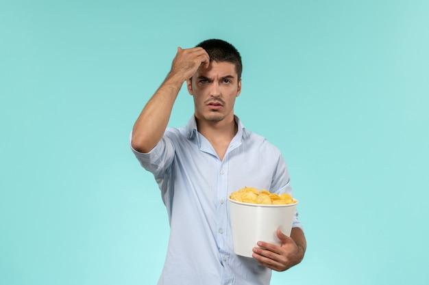 青い机の上にジャガイモのcipsを保持している正面図若い男孤独なリモート男性映画館