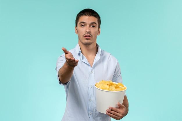 Вид спереди молодой человек, держащий картофельные чипсы на синей стене одинокий удаленный мужской кинотеатр