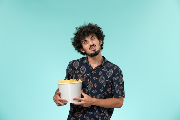 Вид спереди молодой человек, держащий картофельные чипсы на синей стене кино, кино, кинотеатр, мужчина
