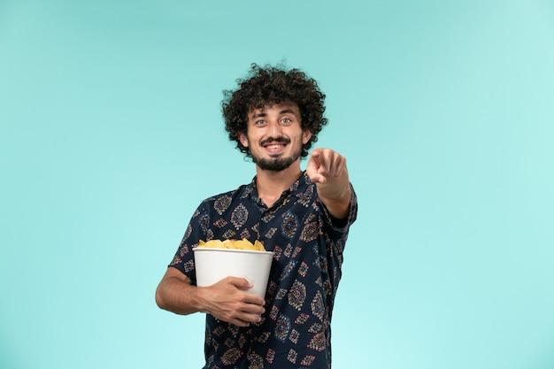 青い壁の男性の映画館の映画フィルム劇場でジャガイモのcipsを保持している正面図若い男