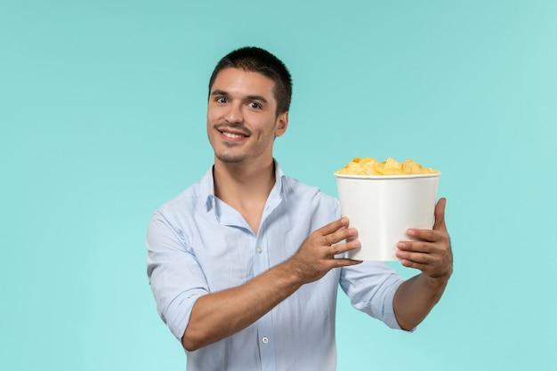 Giovane di vista frontale che tiene le patatine fritte e guardare film che sorride sul cinema remoto solitario di film della parete blu