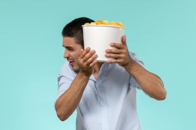 Giovane di vista frontale che tiene le patatine fritte mentre guarda film sul cinema maschio remoto solitario della parete blu