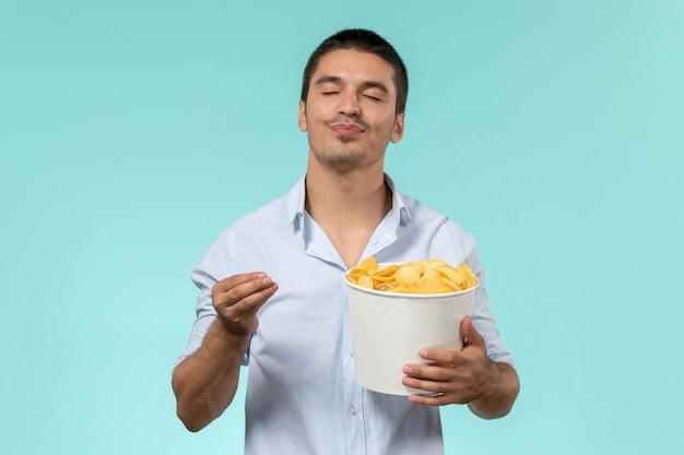 Giovane di vista frontale che tiene le patatine fritte mentre guarda film su un cinema maschio remoto solitario di film di parete blu
