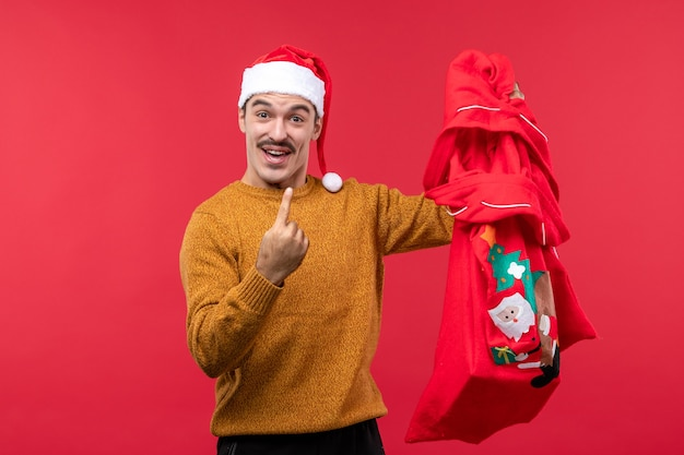 Front view of young man holding present bag on a red wall