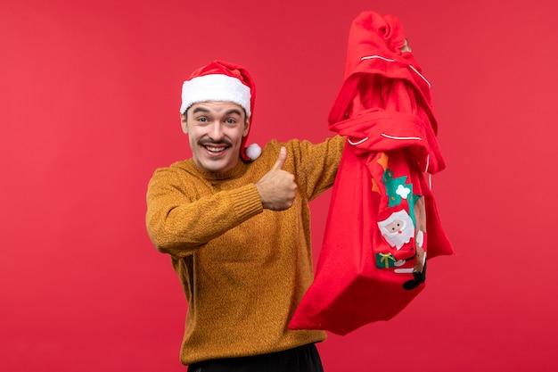 Vista frontale del giovane che tiene presente borsa sulla parete rossa